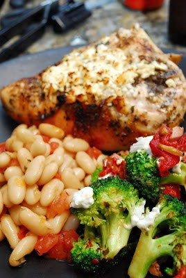 Baked Feta Chicken With Broccoli Red Pepper And Goat Cheese On A Plate