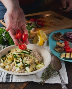 Adding tomatoes to barley salad